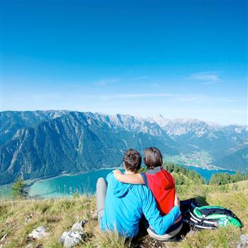 Couple enjoys the view of the lake from the mountain above