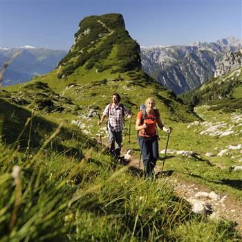 Paar beim Wandern mit Wanderstöcken in den Bergen